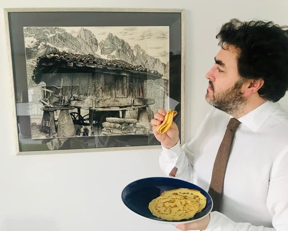 Jonás Fernández comiendo frixuelos y mirando un cuadro de un horreo