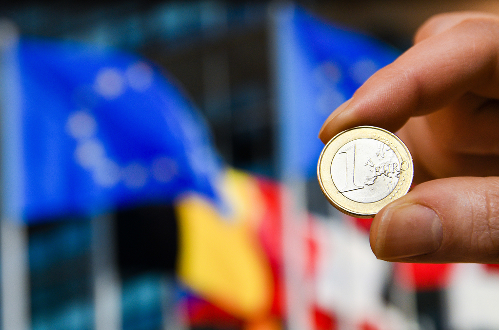 Moneda de euro con fondo banderas europeas